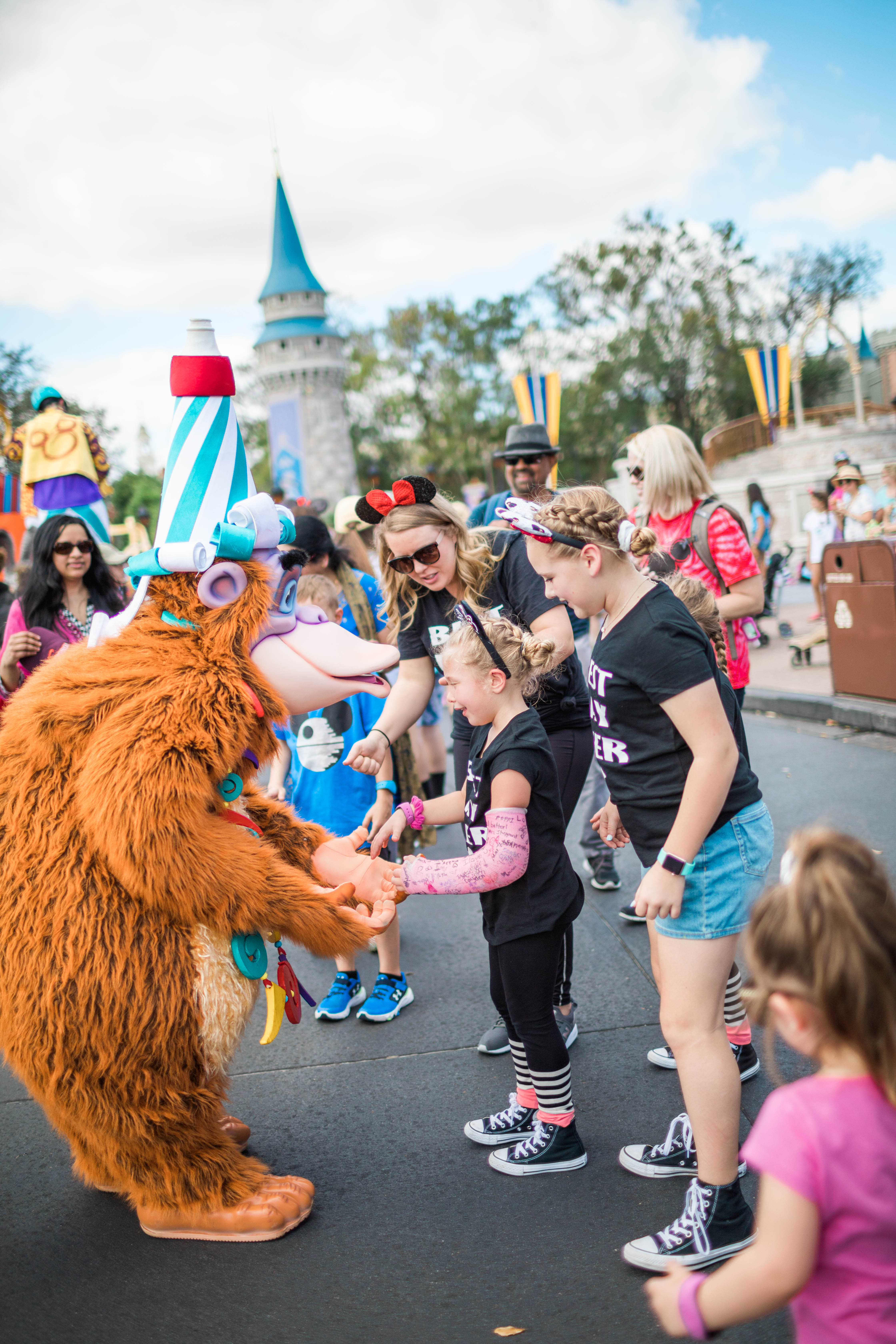 Kids, Mom and Characters dancing in the street at Disney World