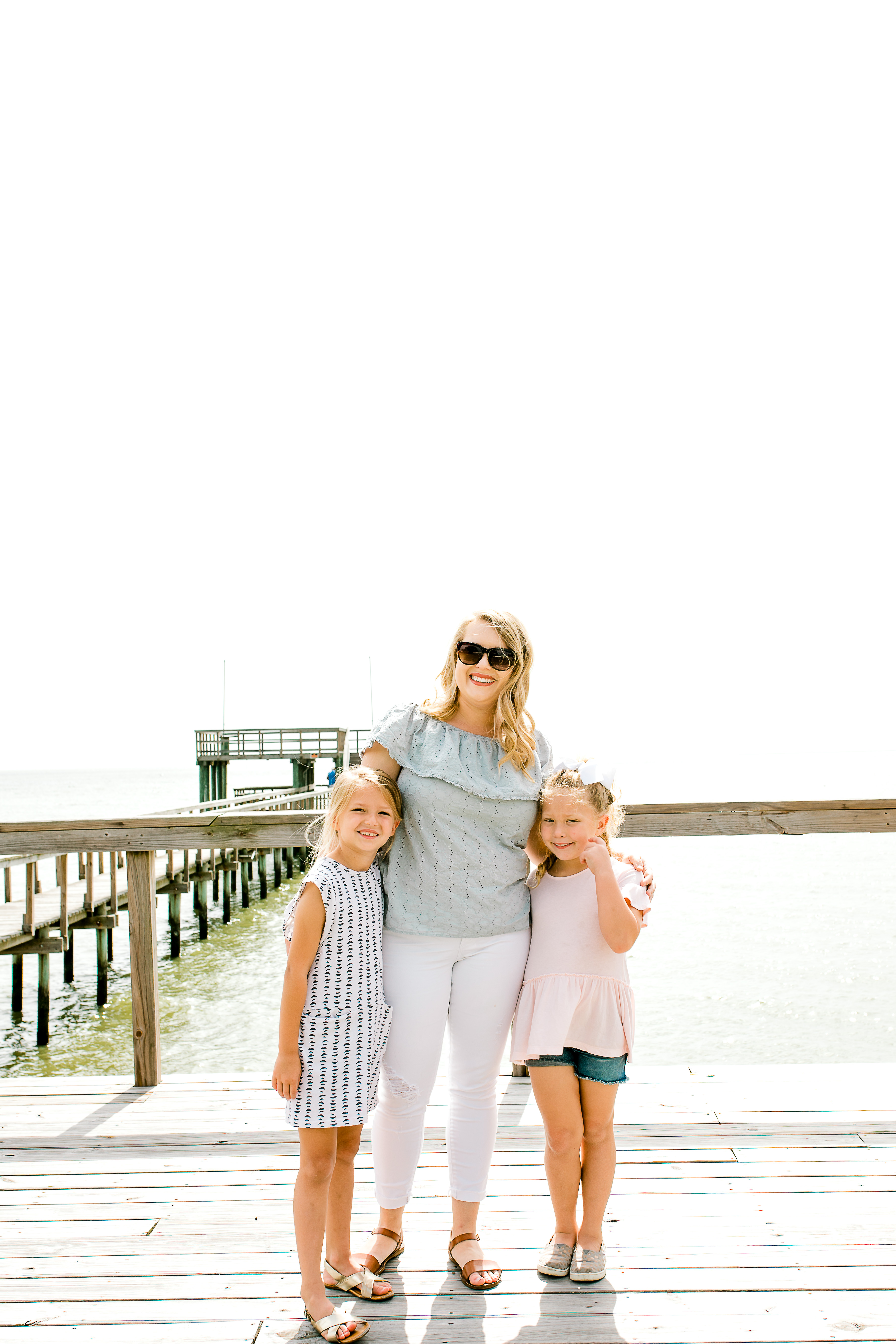 Mom and daughters smiling together on dock near beach.